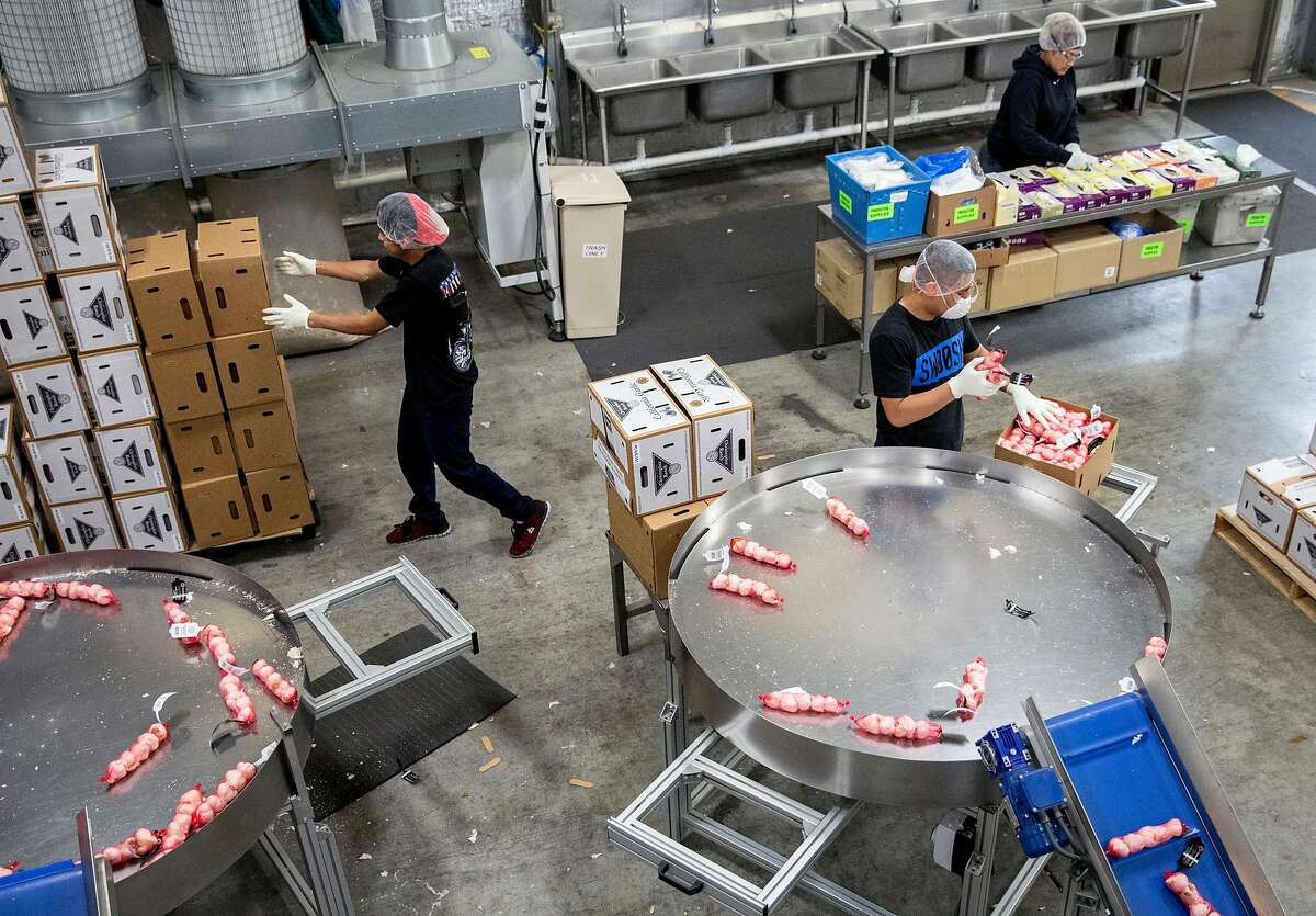 Workers package bulbs of garlic for specialty store orders at the Christopher Ranch garlic farm in Gilroy, Calif. Wednesday, May 15, 2019.