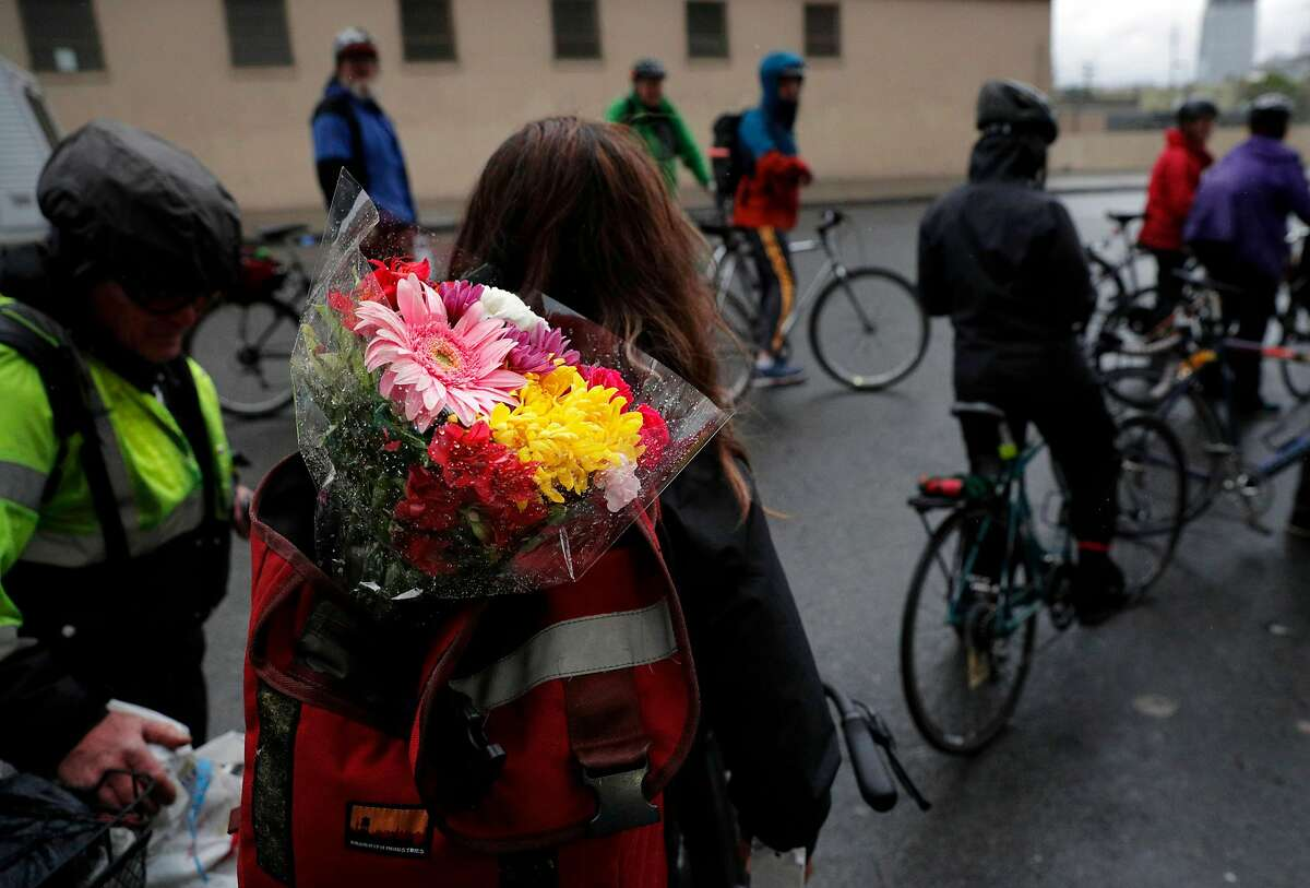 Stefania Siragusa carries flowers in her backpack during the Ride of Silence honoring killed cyclists in San Francisco, Calif., on Wednesday, May 15, 2019. Every year, San Francisco cyclists convene for a Ride of Silence to visit the memorials of people killed while riding through the city's crowded, chaotic streets. Traffic deaths spiked this year after a two-year dip, even as the city rushes to paint crosswalks, widen curbs, put up barriers along bike lanes and make other Vision Zero improvements.