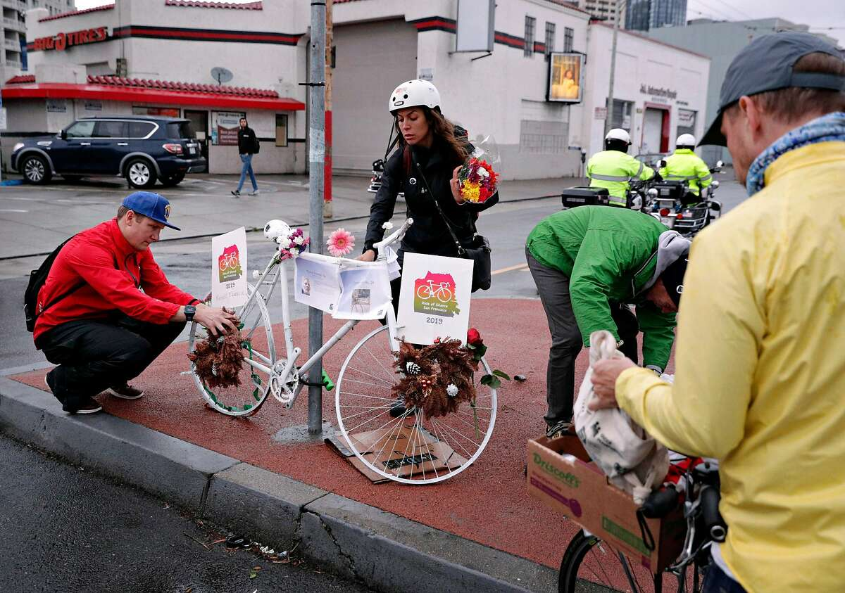 Stefania Siragusa and Taylor Ahlgren place flowers on a Ghost Bike at South Van Ness Avenue and Howard Street during the Ride of Silence honoring killed cyclists in San Francisco, Calif., on Wednesday, May 15, 2019. San Francisco is battling a spike in the number of traffic deaths involving people who are not in cars.