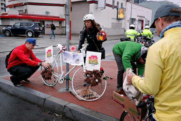 Stefania Siragusa and Taylor Ahlgren place flowers on a Ghost Bike at South Van Ness Avenue and Howard Street during the Ride of Silence honoring killed cyclists in San Francisco, Calif., on Wednesday, May 15, 2019. Every year, San Francisco cyclists convene for a Ride of Silence to visit the memorials of people killed while riding through the city's crowded, chaotic streets. Traffic deaths spiked this year after a two-year dip, even as the city rushes to paint crosswalks, widen curbs, put up barriers along bike lanes and make other Vision Zero improvements.