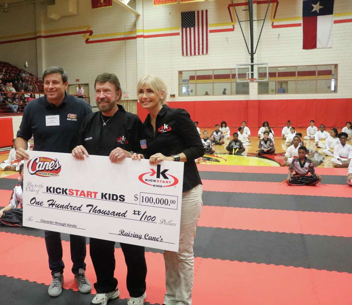Kickstart Kids Chairs Chuck and Gena Norris receive a $100,000 donation from Raising Cane's CEO Todd Graves during Stafford MSD Kickstart Kids Belt Ceremony on Wednesday, May 8, in Stafford.