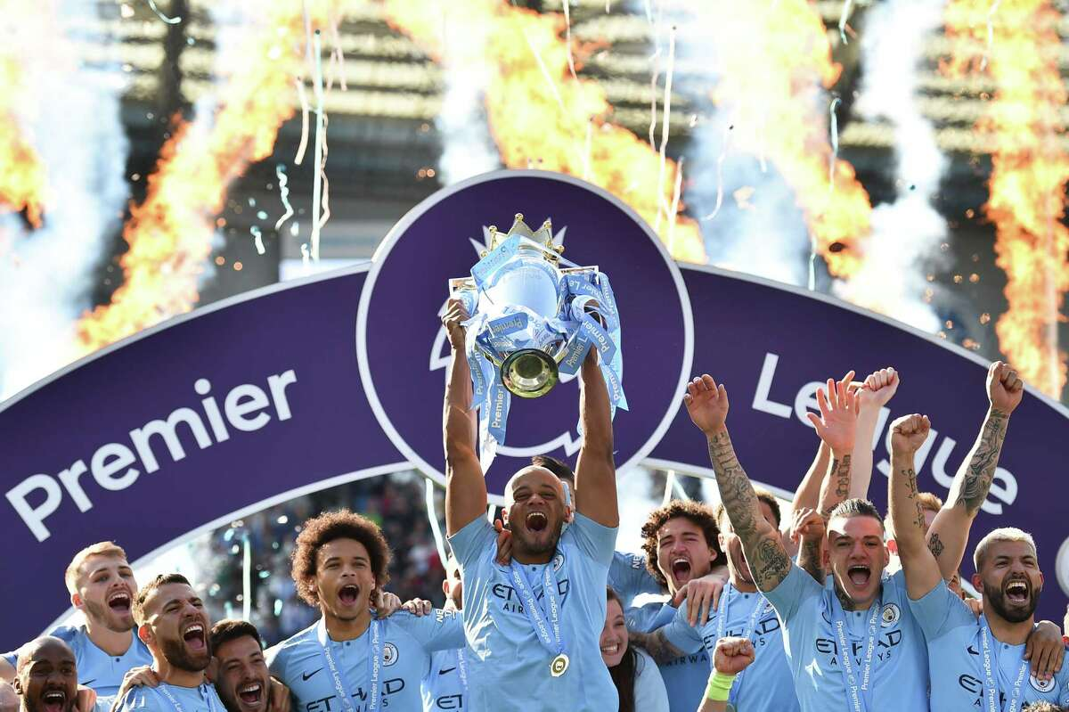 Manchester City's Belgian defender Vincent Kompany (C) holds up the Premier League trophy after their 4-1 victory in the English Premier League football match between Brighton and Hove Albion and Manchester City at the American Express Community Stadium in Brighton, southern England on May 12, 2019. - Manchester City held off a titanic challenge from Liverpool to become the first side in a decade to retain the Premier League on Sunday by coming from behind to beat Brighton 4-1 on Sunday. (Photo by Glyn KIRK / AFP) / RESTRICTED TO EDITORIAL USE. No use with unauthorized audio, video, data, fixture lists, club/league logos or 'live' services. Online in-match use limited to 120 images. An additional 40 images may be used in extra time. No video emulation. Social media in-match use limited to 120 images. An additional 40 images may be used in extra time. No use in betting publications, games or single club/league/player publications. / GLYN KIRK/AFP/Getty Images