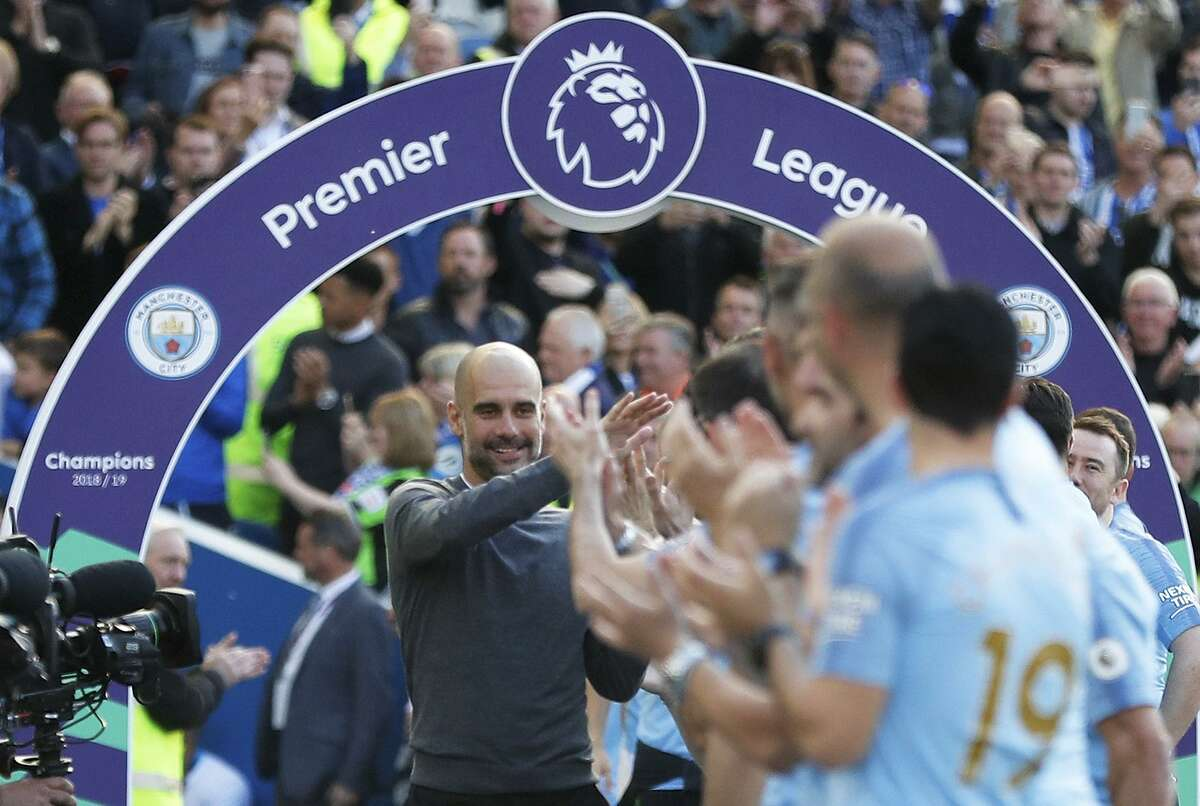 Manchester City coach Pep Guardiola celebrates with the players after the English Premier League soccer match between Brighton and Manchester City at the AMEX Stadium in Brighton, England, Sunday, May 12, 2019. Manchester City defeated Brighton 4-1 to win the championship. (AP Photo/Frank Augstein)