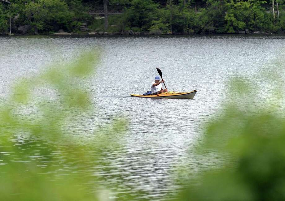 """John Pettit of New Fairfield kayaks across Ball Pond in New Fairfield Thursday, June 7, 2018, - a routine that he follows everyday during the mild seven months of the year. """"It's good exercise,"""" he says. Photo: Carol Kaliff / Hearst Connecticut Media / The News-Times"""