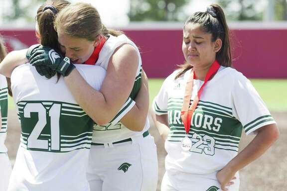 The Woodlands Christian Academy starting pitcher Faith Hanshaw hugs Reagan Robicheaux beside Mariska Cohelo after losing to Waco Reicher 10-2 in the TAPPS Division III state championship game at The Ballparks in Crosby, Thursday, May 16, 2019, in Crosby.