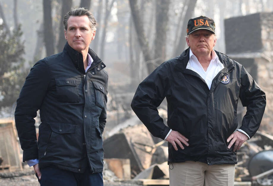 FILE-- US President Donald Trump (C) looks on with Governor of California Jerry Brown (R) and Lieutenant Governor of California, Gavin Newsom, as they view damage from wildfires in Paradise, Calif.on Nov. 17, 2018. The Trump administration on Thursday followed through with its plan to pull more than $900 million in federal funds from California's beleaguered high-speed rail project. Photo: Saul Loeb / AFP / Getty Images