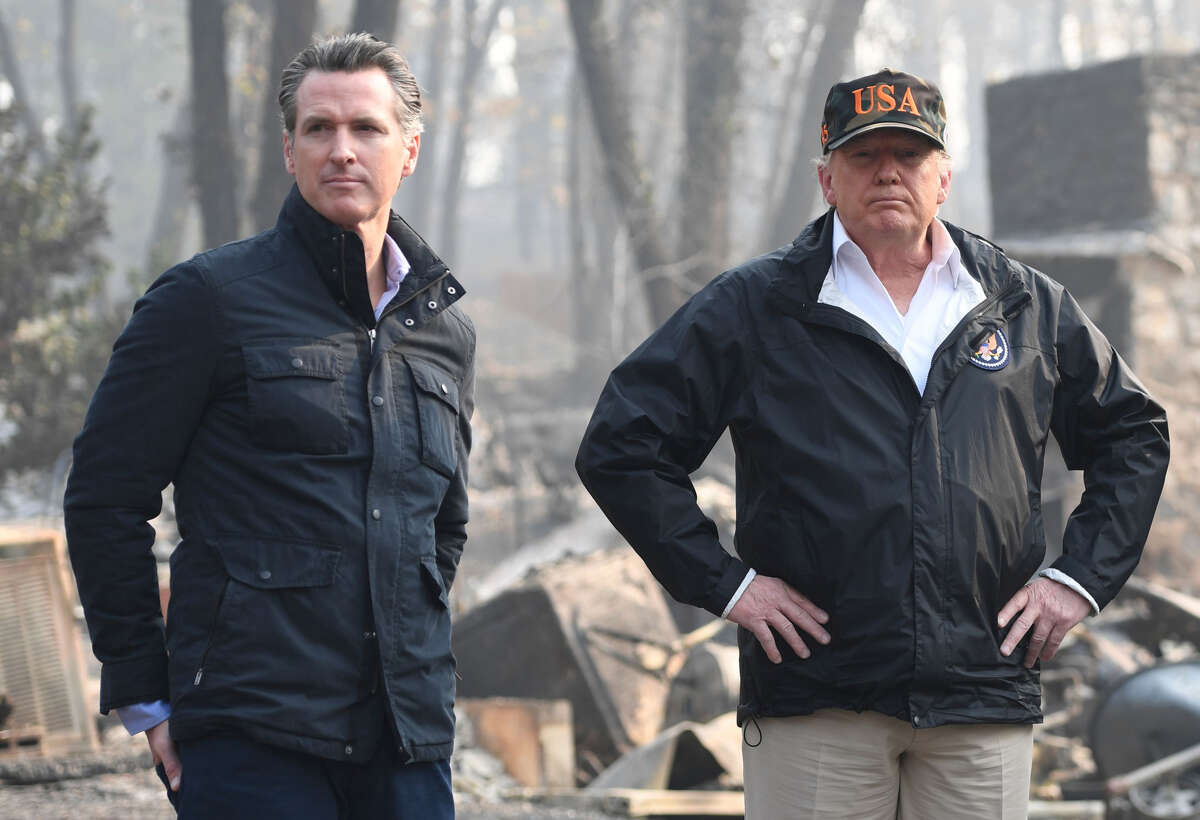 FILE-- US President Donald Trump (C) looks on with Governor of California Jerry Brown (R) and Lieutenant Governor of California, Gavin Newsom, as they view damage from wildfires in Paradise, Calif.on Nov. 17, 2018.The Trump administration on Thursday followed through with its plan to pull more than $900 million in federal funds from California's beleaguered high-speed rail project.