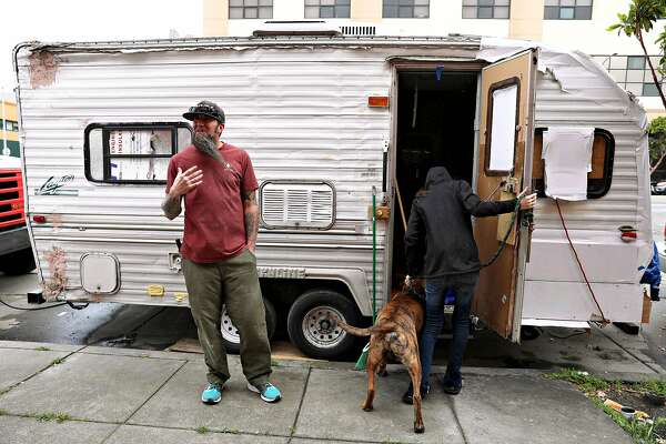 James Janisse (left) stands outside the travel trailer he lives in as his wife Lisa Janisse (right) returns from walking their dog, Kodiak (center), on Thursday, May 16, 2018 in San Francisco, Calif.