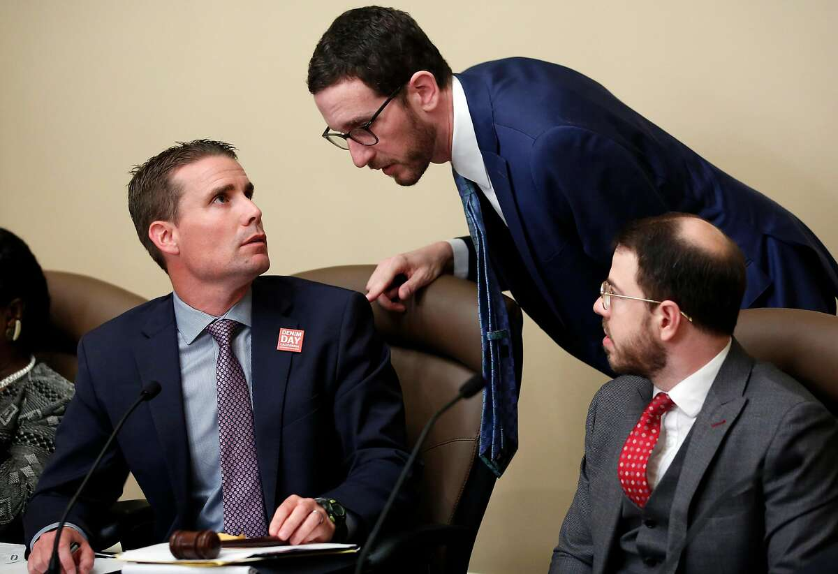State Sen. Mike McGuire, D-Healdsburg, left, confers with State Sen. Scott Wiener, D-San Francisco, center, during a hearing on their housing bills Wednesday, April 24, 2019, in Sacramento, Calif. McGuire merged his bill, SB4 with Wiener bill, SB50 that would increase housing near transportation and job hubs. The bill was approved by the Senate Governance and Finance Committee. (AP Photo/Rich Pedroncelli)