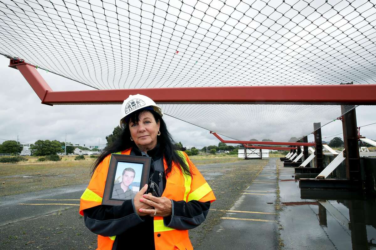 """Dayna Whitmer holds a portrait of her son, Mattie, who at the age of 20 jumped from the Golden Gate Bridge on November 15, 2017, as she poses for a photograph at the Richmond Yard in Richmond, Calif., on Thursday, May 16, 2019. His body was never recovered. Whitmer, of Hercules, is standing underneath a suicide deterrent system net that will prevent anyone from easily jumping into the water below. """"People were so upset; they thought it would ruin the look of the bridge and say it's going to make it ugly and it's not,"""" Whitmer said. """"It doesn't matter because it is a bridge and the net's only going to help."""""""