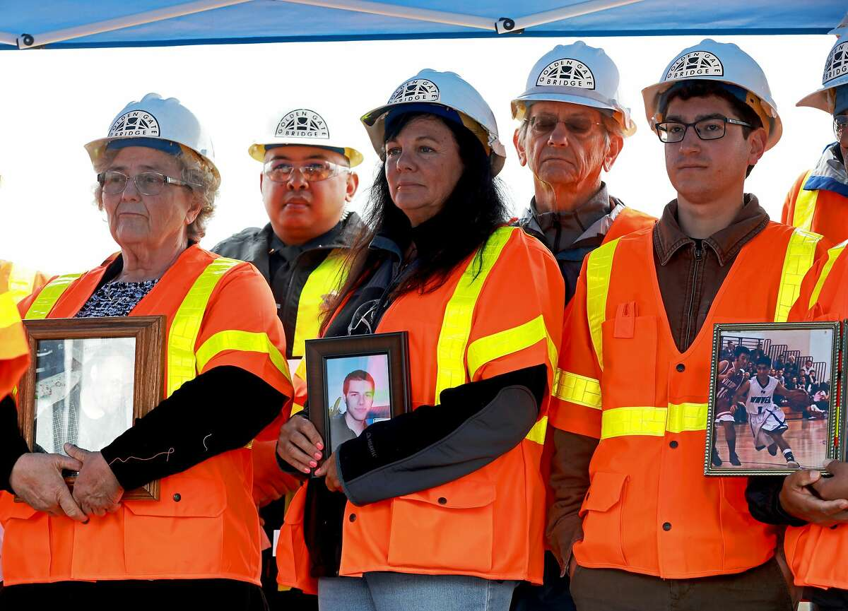 """Dayna Whitmer (center) stands with other family members who've lost loved ones to jumping suicides during a press conference introducing a suicide deterrent system net at Richmond Yard in Richmond, Calif., on Thursday, May 16, 2019. Whitmer's son, Mattie, who at the age of 20, jumped from the Golden Gate Bridge on November 15, 2017. His body was never recovered. The net will be placed 20 feet below the sidewalk, extending 20 feet out from the Golden Gate Bridge. It will prevent anyone from easily jumping into the water below. """"People were so upset; they thought it would ruin the look of the bridge and say it's going to make it ugly and it's not,"""" Whitmer, of Hercules, said. """"It doesn't matter because it is a bridge and the net's only going to help."""""""