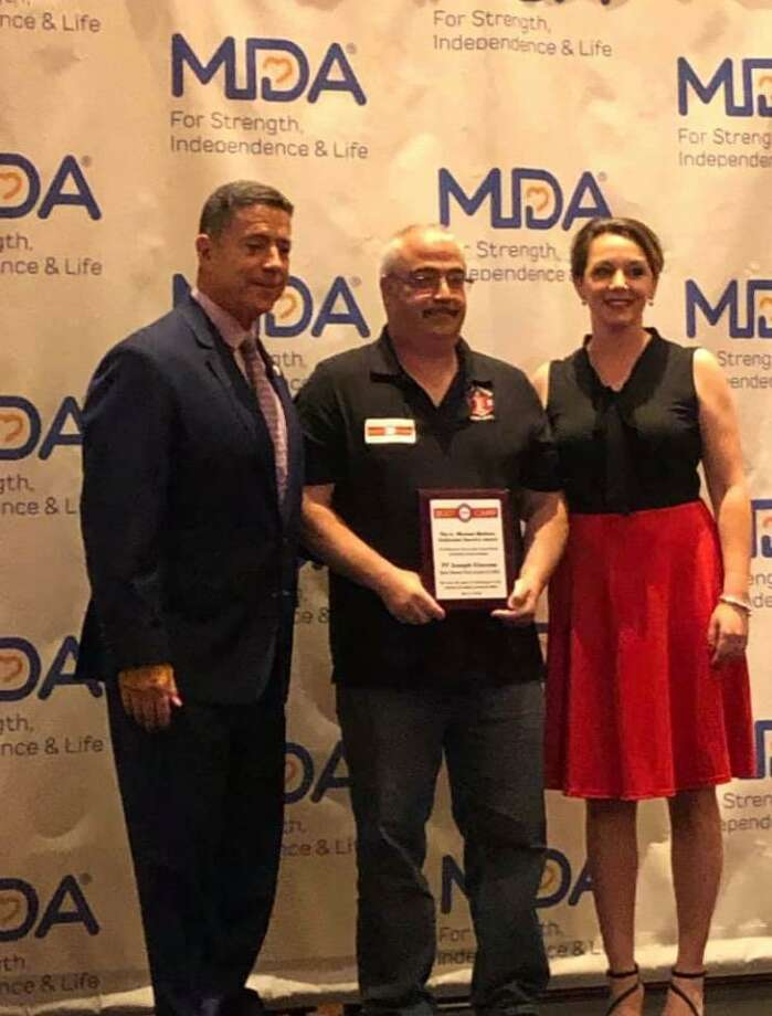 Firefighter Joe Ciscone, center, receives the A. Michael Mullane Devoted Service Award at the International Association of Firefighters and Muscular Dystrophy Association's annual Boot Camp May 6 at Mohegan Sun. Joining him are Jay Colbert, left, IAFF 3rd District vice president, and MDA of Connecticut Development Specialist Krista Nieves. Photo: Joe Ciscone / Contributed Photo