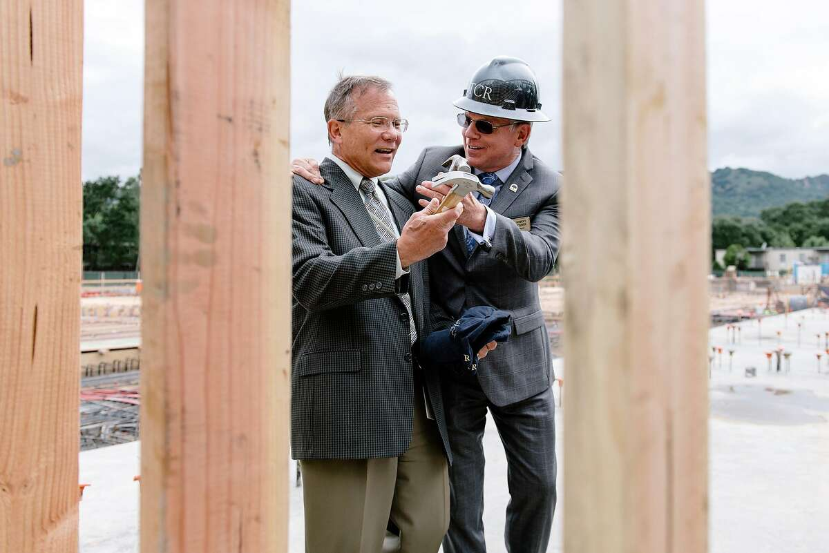 Danville mayor Robert Storer, right, hands town manager Joe Calabrigo a hammer for a nail driving ceremony during an Alexan Downtown Danville multifamily housing development framing ceremony in Danville, Calif, on Wednesday, May 15, 2019.