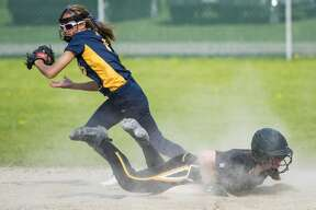 Midland's Emerson Hoon tries to tag the base as Dow's Kathryn Altes slides during the Coaches Versus Cancer softball game at Dow High School on Thursday. (Danielle McGrew Tenbusch/for the Daily News)