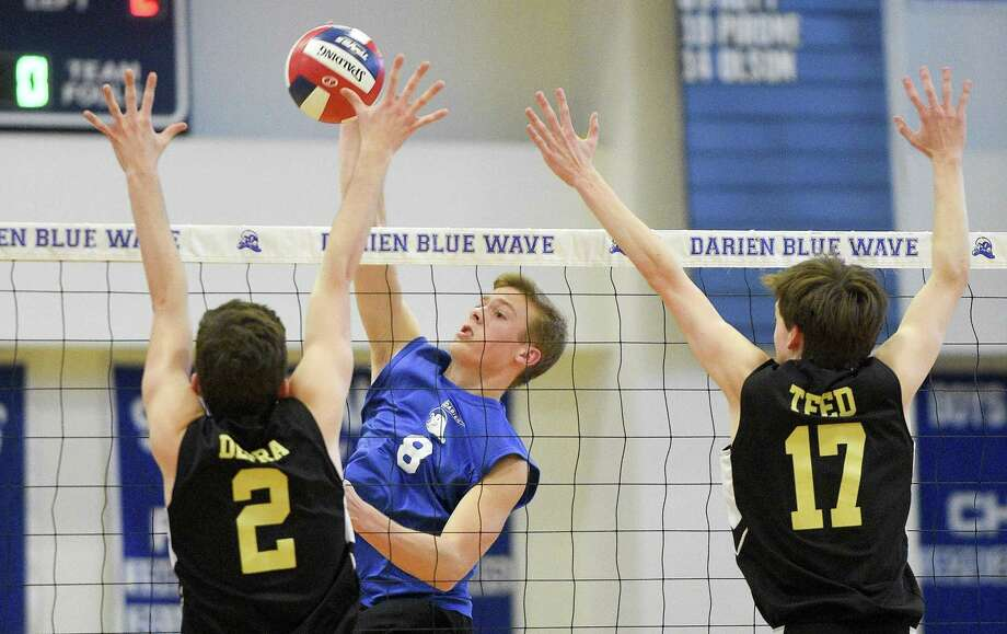 Darien's Tyler Herget (8) slams the ball past Joel Barlow's Aidan Depra (2) and Carson Teed on Thursday. Darien won 3-0 (25-12, 25-15, 25-22), closing the regular season for both teams. Photo: Matthew Brown / Hearst Connecticut Media / Stamford Advocate