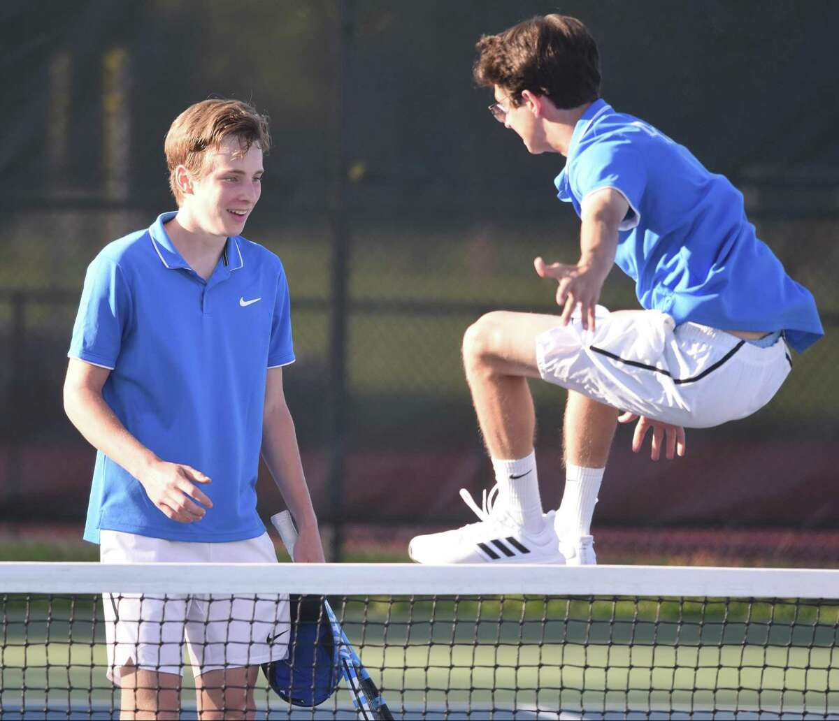 Darien's Tyler Cramer leaps in the air to celebrate with Nick Derby after Derby's win at No. 3 singles clinched a match victory for the Wave in their FCIAC boys tennis semifinal in New Canaan on Thursday, May 16, 2019.