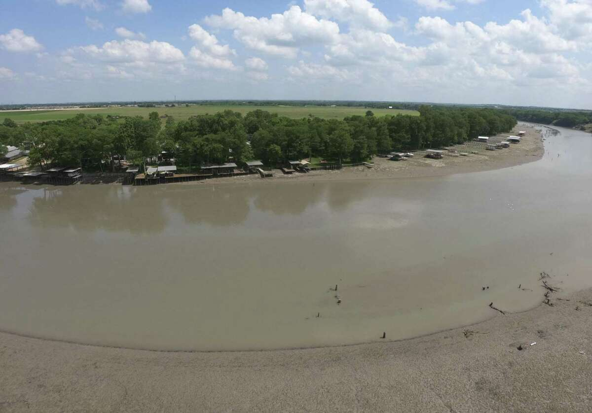 The draining of Lake Dunlap has left shallow muddy water and a muddy bank that was underwater until a partial dam collapse on the south end of the lake on Tuesday morning. Much of the water has drained into the Guadalupe River. The water levels have fallen dramatically.