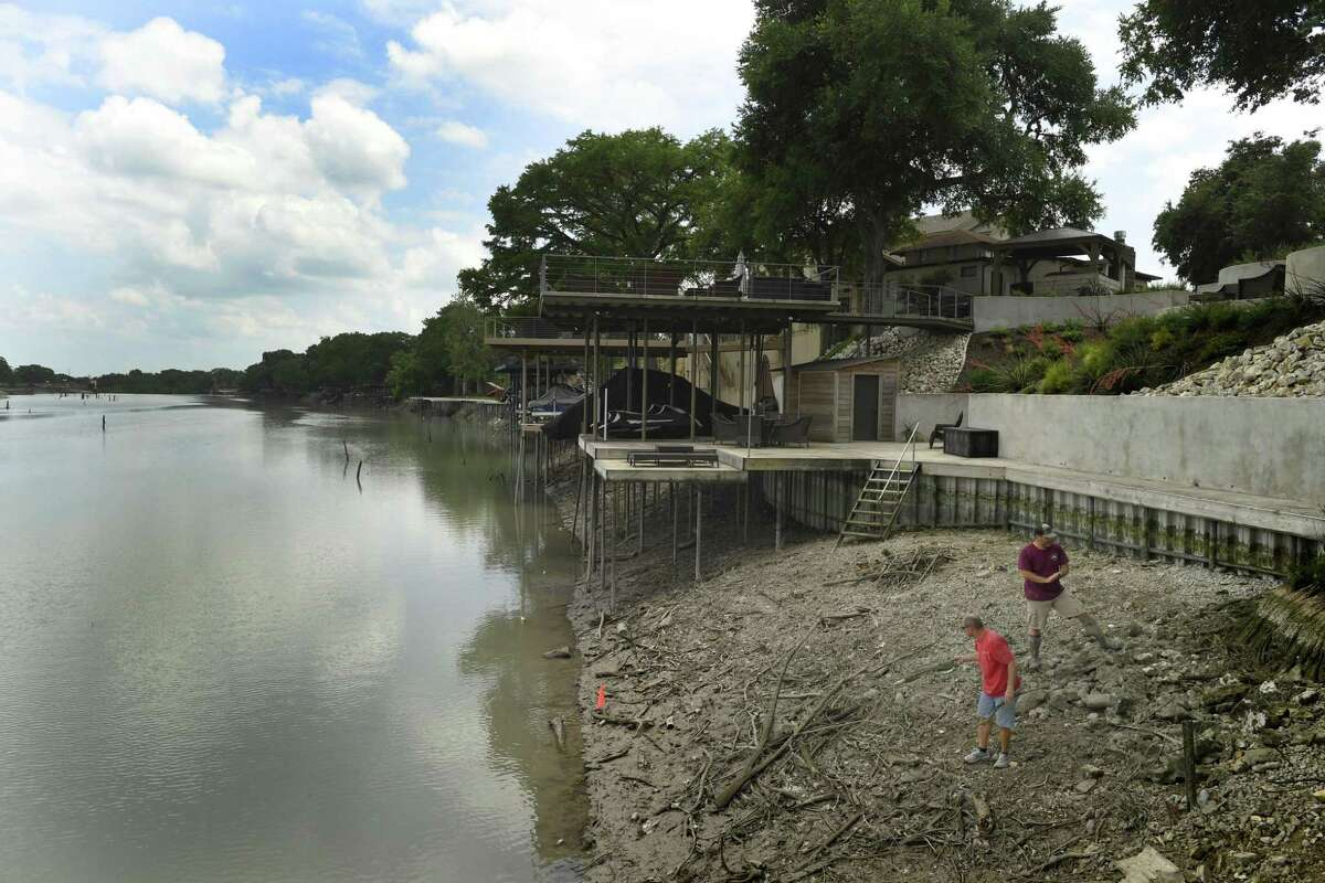 Daryl Payne, bottom, and Mark Worley work to clear debris from the newly exposed bank of Lake Dunlap on Payne's property on Wednesday afternoon, May 15, 2019. A partial dam collapse on the south end of Lake Dunlap on Tuesday morning has caused much of the lake to drain into the Guadalupe River. The water levels have fallen dramatically with no end in sight.