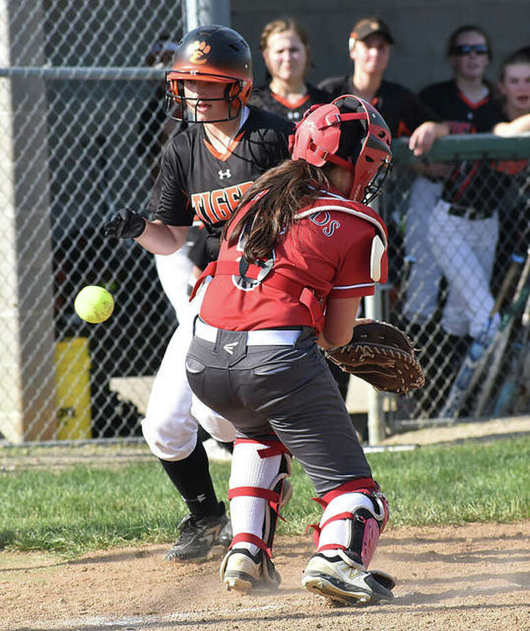 Edwardsville's Sydney Lawrence scores in the fourth inning as the ball gets away from Alton catcher Audrey Evola on Thursday in Alton. Photo: Matt Kamp/The Intelligencer
