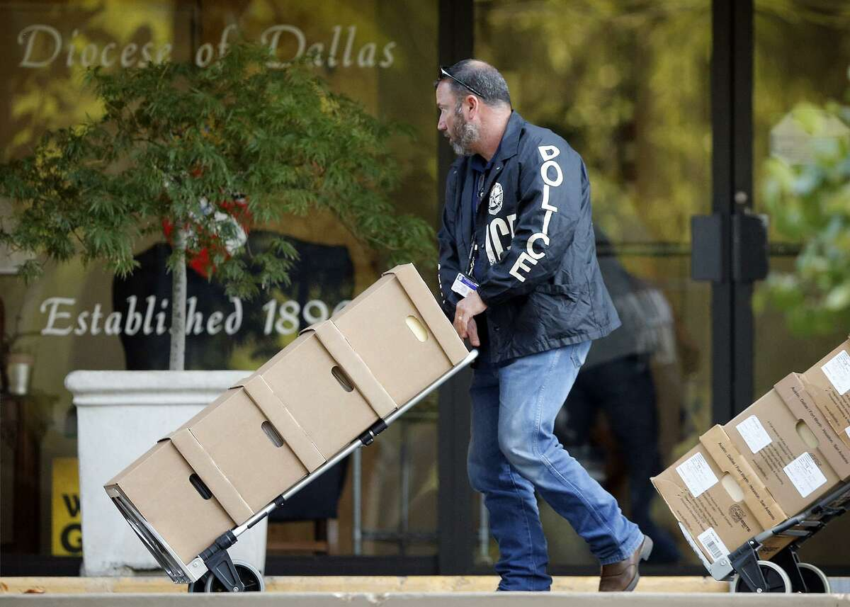 Dallas police officials cart out boxes from a raid on the Catholic Diocese of Dallas on Wednesday, May 15, 2019. Dallas police officers on Wednesday morning raided several Dallas Catholic Diocese offices after a detective said church officials have not cooperated with investigations into sexual abuse by its past clergy members. (Tom Fox/Dallas Morning News/TNS)