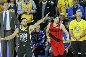 Portland Trail Blazers' Seth Curry and Golden State Warriors' Stephen Curry watch Curry's three-pointer in the fourth quarter during game 2 of the Western Conference Finals between the Golden State Warriors and the Portland Trail Blazers at Oracle Arena on Thursday, May 16, 2019 in Oakland, Calif.