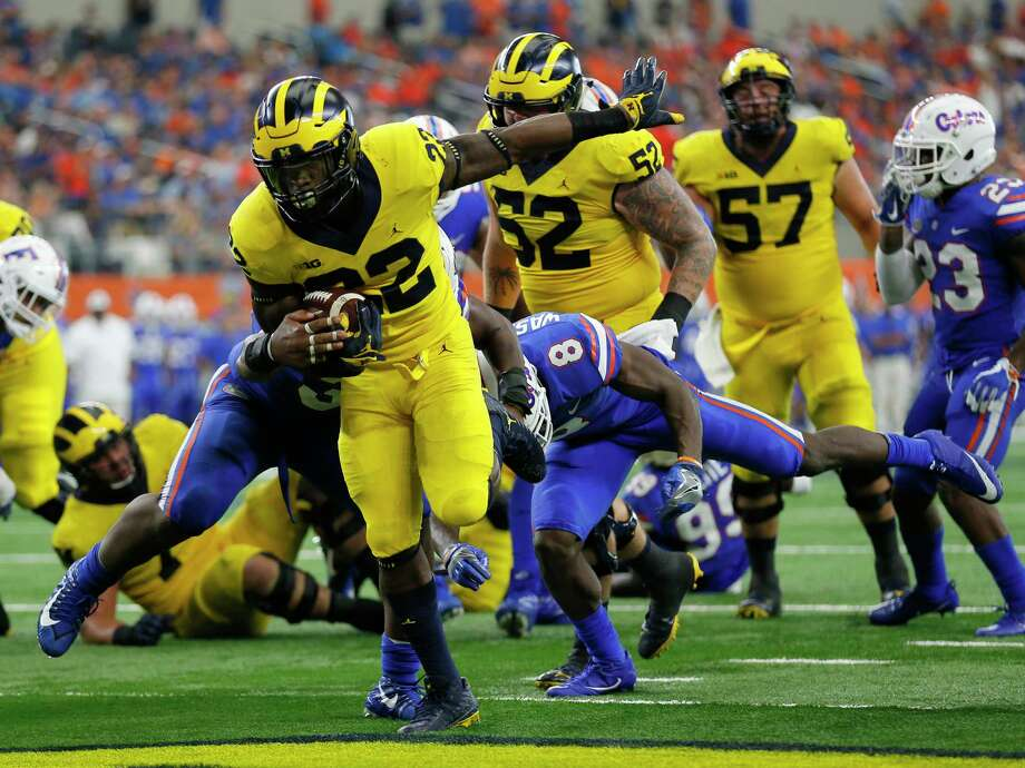 PHOTOS:Players from Houston high schools and Texas college drafted in 2019 Michigan running back Karan Higdon (22) reaches the end zone for at touchdown on a running play after getting through Florida linebacker David Reese, left, and defensive back Nick Washington (8) in the second half of an NCAA college football game, Saturday, Sept. 2, 2017, in Arlington, Texas. (AP Photo/Roger Steinman) >>>A look at players who were taken in the 2019 NFL Draft that went to Houston high schools or Texas colleges ... Photo: Roger Steinman, Associated Press / Internal