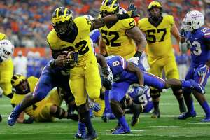 Michigan running back Karan Higdon (22) reaches the end zone for at touchdown on a running play after getting through Florida linebacker David Reese, left, and defensive back Nick Washington (8) in the second half of an NCAA college football game, Saturday, Sept. 2, 2017, in Arlington, Texas. (AP Photo/Roger Steinman)