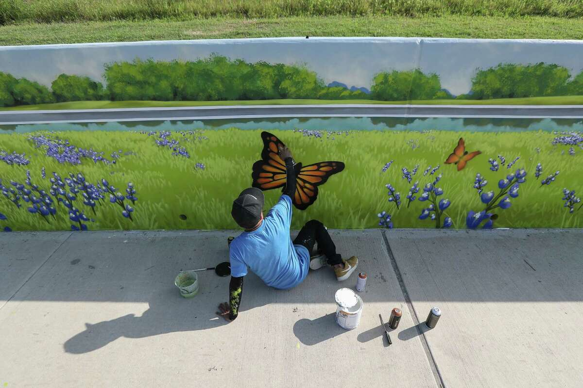 Local artist Gelson D. Lemus aka w3r3on3 works on a mural dedicated to the late-Council Member Larry Green on his birthday prior to the Sims Bayou Trail mural dedication Thursday, May 16, 2019, in Houston.