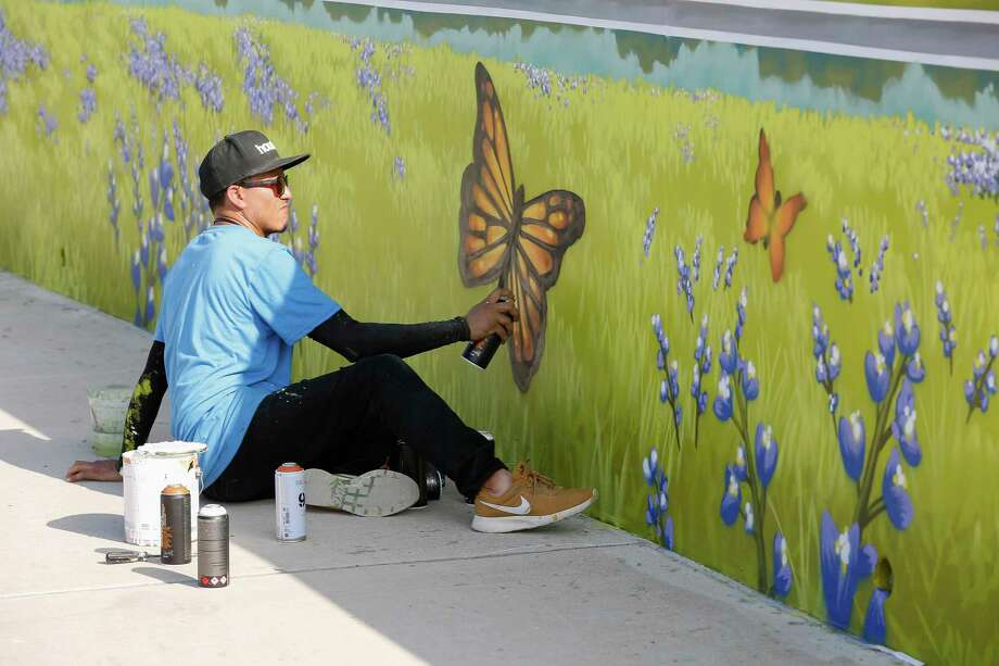 Local artist Gelson D. Lemus aka w3r3on3 works on a mural dedicated to the late-Council Member Larry Green on his birthday prior to the Sims Bayou Trail mural dedication Thursday, May 16, 2019, in Houston. Photo: Steve Gonzales, Staff Photographer / © 2019 Houston Chronicle