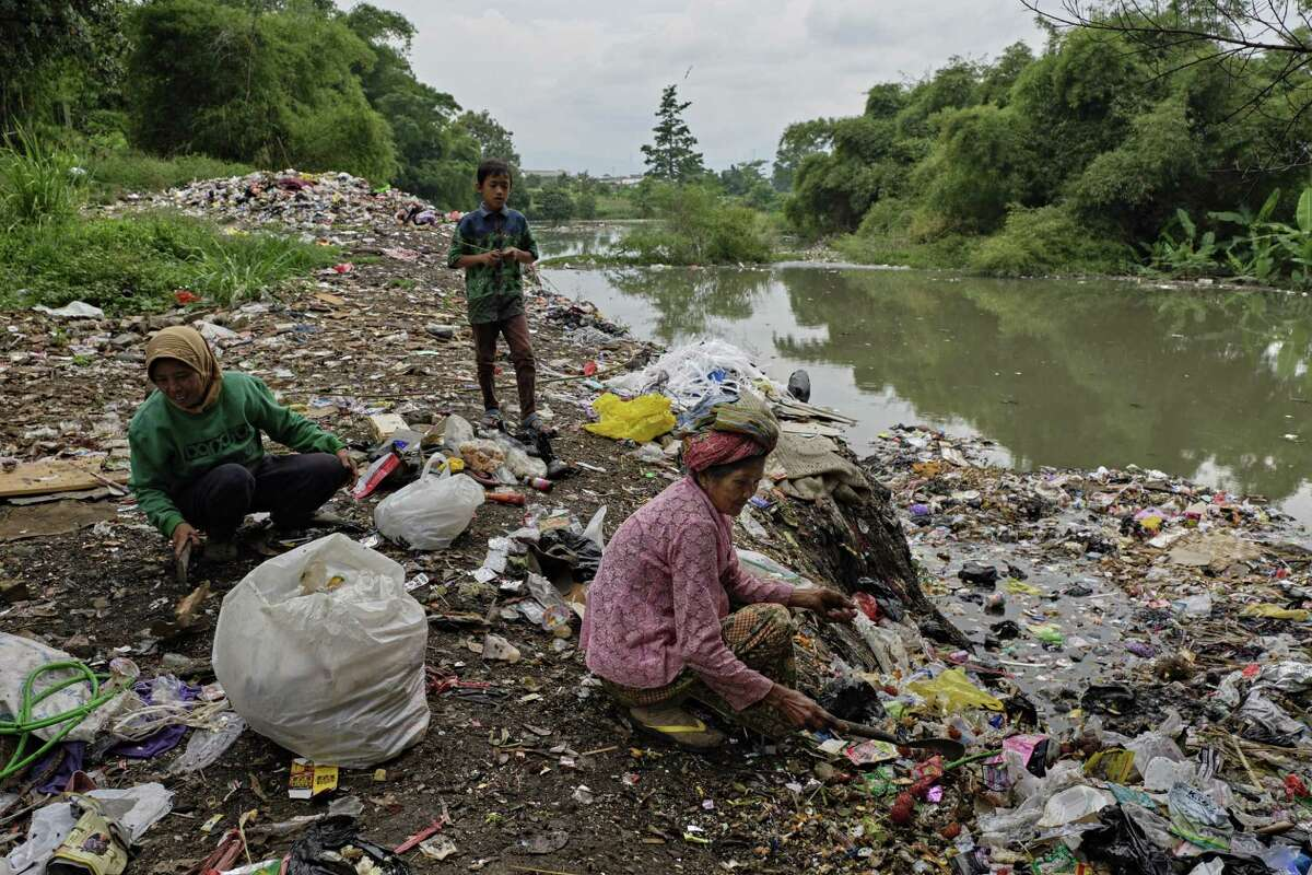 Villagers collect plastic waste left by high water during the rainy season along the banks of a tributary of the Citarum river on January 14, 2019 outside Bandung, Java, Indonesia.