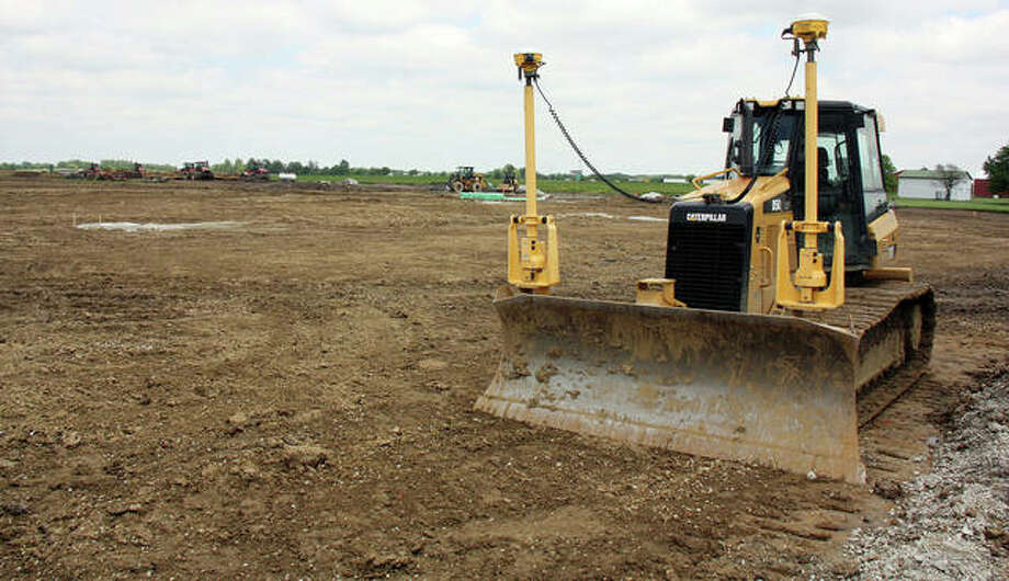 The former farm fields have been flattened in some places and dug up in others as construction workers install sewer pipes and create the park's main road. This image was taken Wednesday. Photo: Charles Bolinger | The Intelligencer