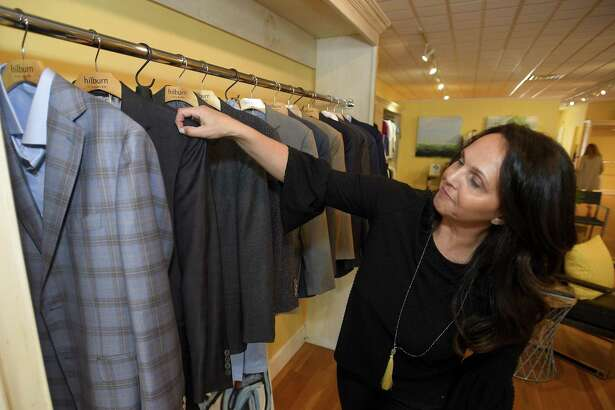 Lisa Lombardi, an independent personal Stylist for the J.Hilburn men's clothing brand, looks through a rack at the J.Hilburn pop-up shop on May 7, 2019, at 95 Bedford St., in downtown Stamford, Conn.