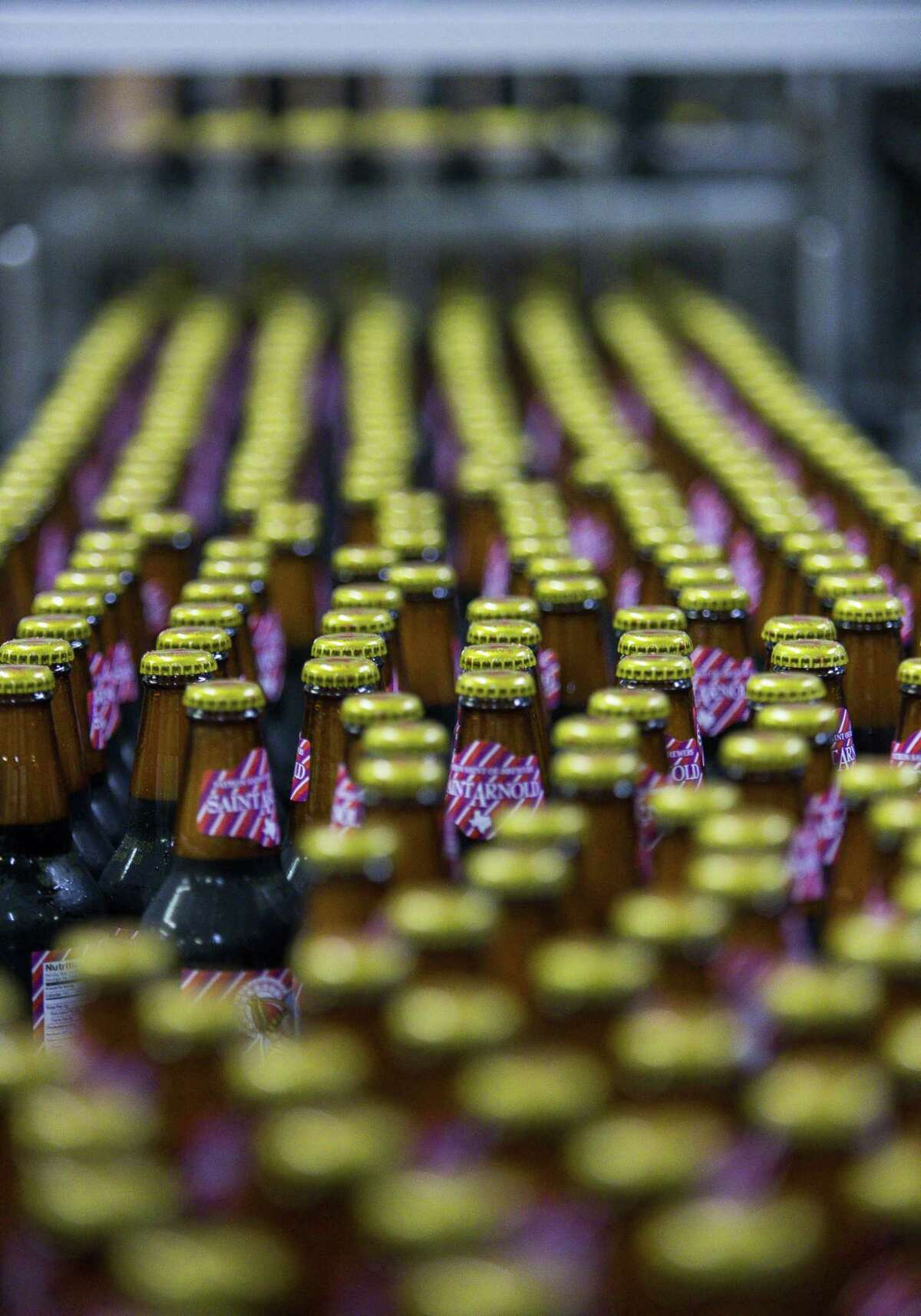 Bottles of Saint Arnold Brewing Company Root Beer make their way down a conveyer to be packaged at the brewery's facility just outside of downtown Houston, Wednesday, May 15, 2019. The brewery, started by Brock Wagner, will celebrate its 25th anniversary this June. Wagner started experimenting with brewing as an undergrad at Rice University, and after leaving his first career in finance, he started Houston's oldest craft brewery in 1994.