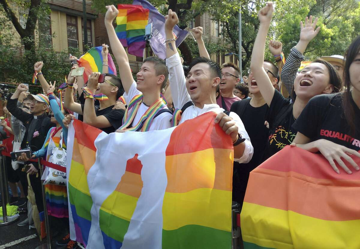 Same-sex marriage supporters cheer outside the Legislative Yuan Friday, May 17, 2019, in Taipei, Taiwan after the legislature passed a law allowing same-sex marriage in a first for Asia. The vote Friday allows same-sex couples full legal marriage rights, including in areas such as taxes, insurance and child custody. (AP Photo/Chiang Ying-ying)