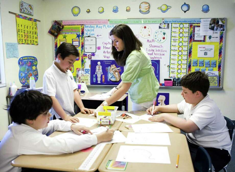 Whitney Finn, center top, a 4th grade teacher at Villa Maria School works with students Sean Puente, left, Ryan Park, second from left, and Christian Conte, right, during a class about identifying body parts. Photo: Kerry Sherck / ST
