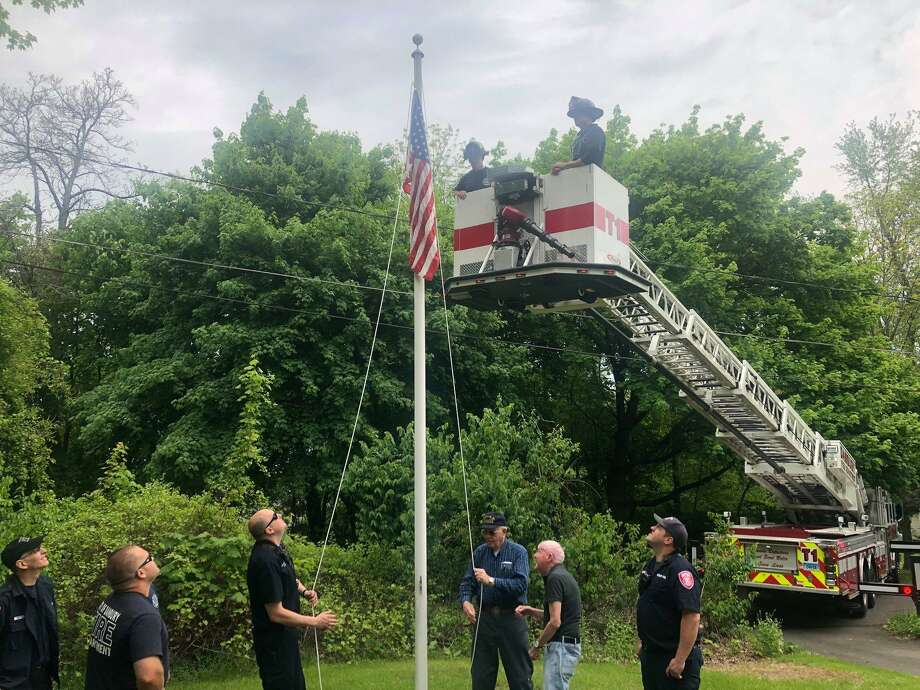 Danbury firefighters help two Korean War veterans restring a flagpole Monday, May 17, 2019. Photo: Danbury Fire Department / Facebook