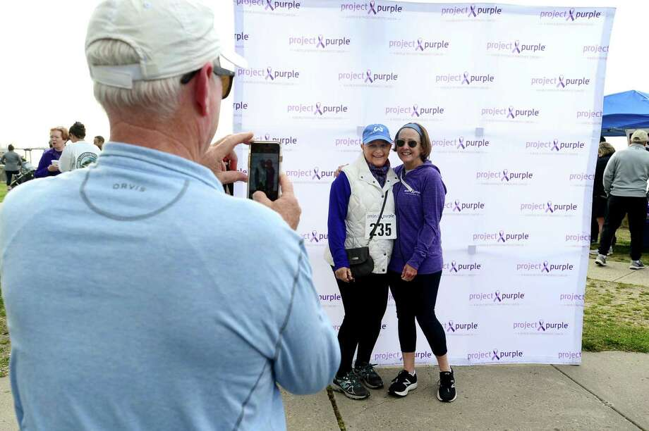 Jerry Lillis of Westport takes a photo of survivor Karen Vendetti of Wilton and Pam Lillis during The Project Purple Steps for a Cure run and walk to benefit Pancreatic Cancer research Saturday, May 11, 2019, at Calf Pasture Beach in Norwalk, Conn. The event is in memory of lifelong Norwalk resident Donna Cutrone and all those battling pancreatic cancer. Photo: Erik Trautmann / Hearst Connecticut Media / Norwalk Hour