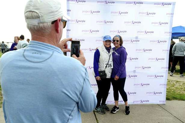Jerry Lillis of Westport takes a photo of survivor Karen Vendetti of Wilton and Pam Lillis during The Project Purple Steps for a Cure run and walk to benefit Pancreatic Cancer research Saturday, May 11, 2019, at Calf Pasture Beach in Norwalk, Conn. The event is in memory of lifelong Norwalk resident Donna Cutrone and all those battling pancreatic cancer.