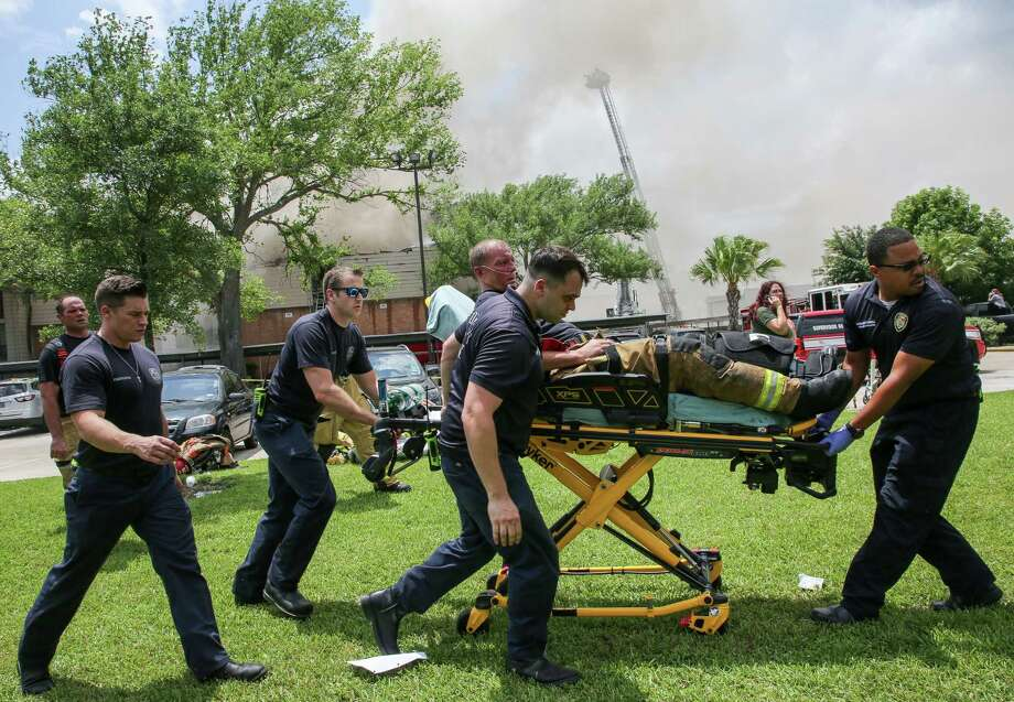 A Houston Fire Department firefighter is transported to an ambulance on a stretchers as the department battles a four-alarm fire on the 3000 block of Greenridge Drive Friday, May 17, 2019, in Houston. Photo: Godofredo A. Vásquez, Staff Photographer / 2019 Houston Chronicle