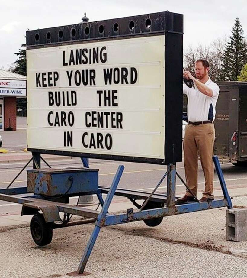 Evan Osentoski, with Osentoski Real Estate in Caro, put up this sign in the former Big Acre parking lot asking the state to keep its promise to build the new state hospital in Tuscola County. (Courtesy Photo)