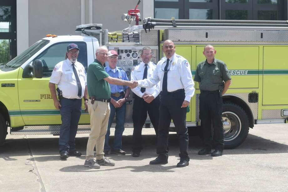 Kenny McBride (left), assistant fire chief for Jones Creek Volunteer Fire Department, Rich Jones, president of Harris County Emergency Services District, Thomas Grissett, treasurer for Jones Creek VFD, David McCollister, captain of Jones Creek VFD and Jeremy Wagner, chief law enforcement for Texas A& Forest Service officially transfer a 2003 mini pumper truck from Klein VFD to Jones Creek VFD. Photo: Chevall Pryce