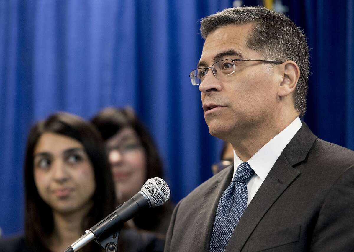 California Attorney General Xavier Becerra stands with members of his legal team as he unveils findings of a report on the state's immigration detention centers during a press conference held at the California Department of Justice office in San Francisco, Calif. Monday, Feb. 18, 2019.