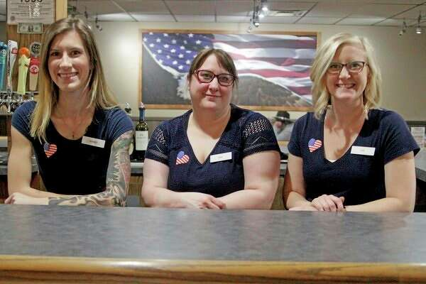 From left, Waitresses Sydney Fulks and Jessica Brade, and manager Lisa Chinoski pose behind the bar at the new Bad Axe Steakhouse, located at 113 S Port Crescent St. in Bad Axe. (Mike Gallagher/Huron Daily Tribune)