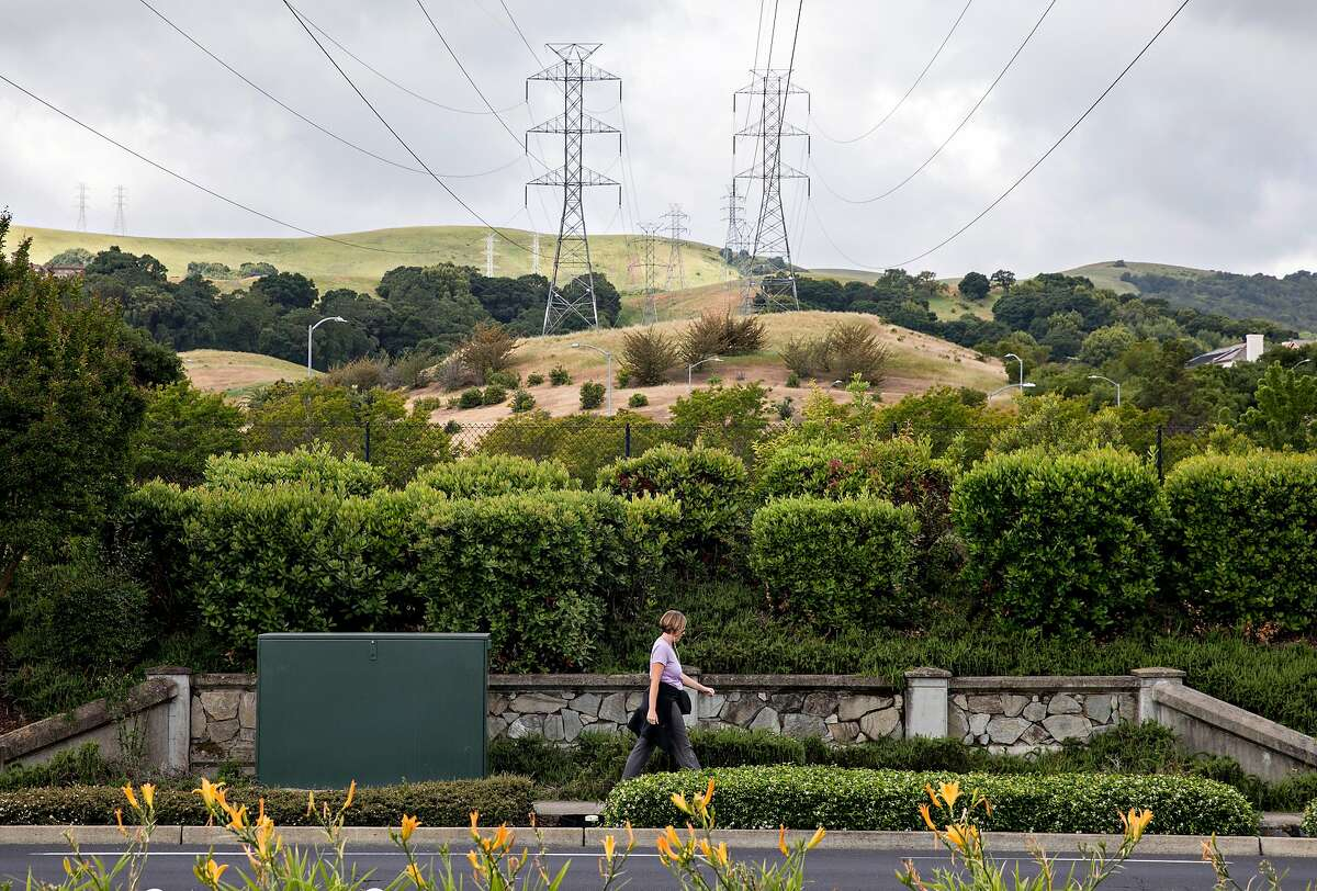 A woman walks underneath high-voltage power transmission lines owned by PG&E stretched across a neighborhood near San Ramon Valley Boulevard in San Ramon, Calif. Friday, May 17, 2019.