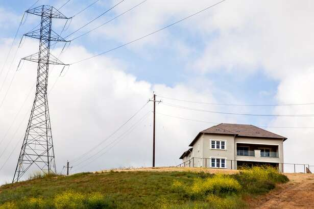 High-voltage power transmission lines owned by PG&E are seen near a newly constructed neighborhood along Dougherty Road in San Ramon, Calif. Friday, May 17, 2019.