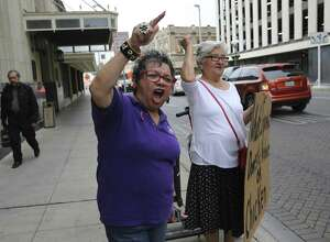 Patricia Castillo, left, director of the P.E.A.C.E. Initiative, a nonprofit that fights domestic violence, leads others at a demonstration hosted by her organization near City Hall on May 1, 2019, to call attention to two San Antonio police reports about domestic violence involving mayoral candidate and City Council member Greg Brockhouse in 2006 and 2009. He was not charged in either case and denied the allegations.