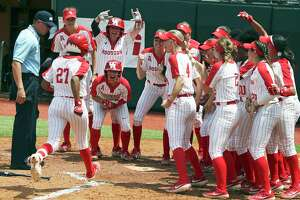 Cougar teammates celebrate at the plate after Arielle James watches her three run homer clear the left field fence as Houston beats Texas A&M 3-1 in the NCAA regional tournament at MCCombs Field in Austin on May 17, 2019.
