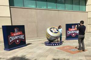 Fans take pictures in front of the oversized Astros World Series championship ring outside Minute Maid Park on Friday, May 17, 2019.