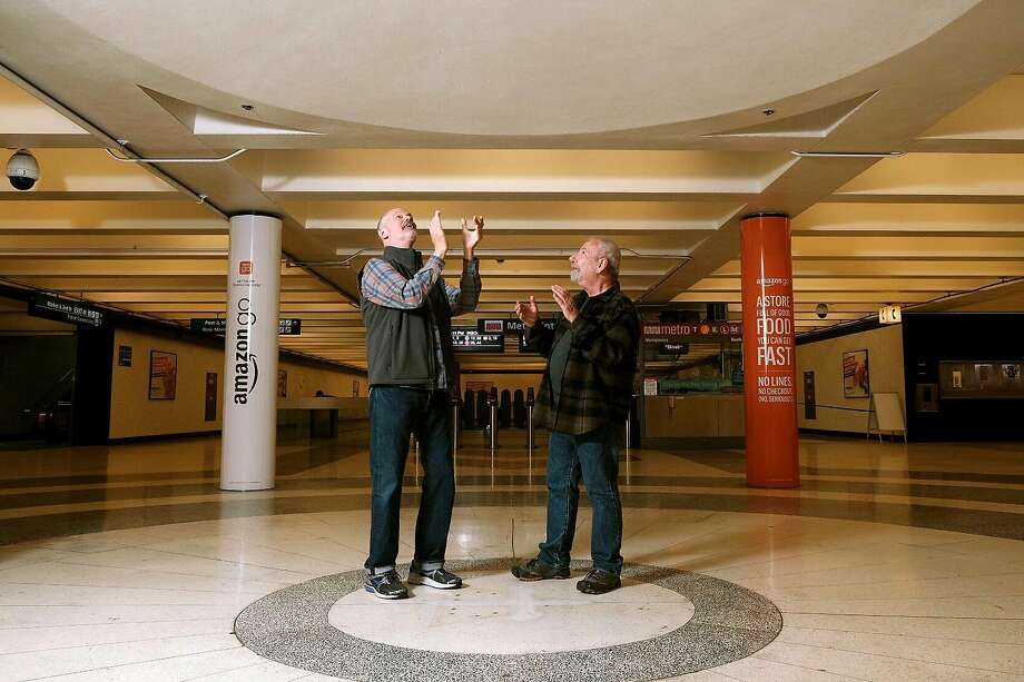 Ken Woods (left) and Tom Kelleher stop and check out the sweet spot at the BART station where a newsstand was removed and now there is an echo chamber. Photo: Michael Short / Special To The Chronicle