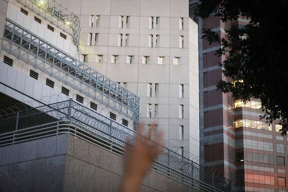 LOS ANGELES, CA - JUNE 14:  A protestor  waves towards cell windows (CENTER and TOP C) where ICE detainees are being held in upper floors of the Metropolitan Detention Center on June 14, 2018 in Los Angeles, California. Protestors at one point chanted 'Yo